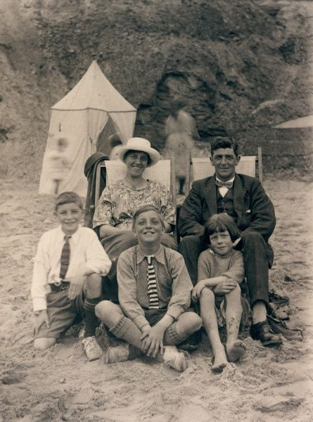 A family of five on holiday. Mother and father sit on deckchairs in their best clothes, with their three children sitting in front on them on the sand. Date: circa 1920s