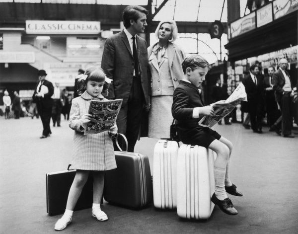 A family wait at a train station. The children sit on their suitcases and read comics while they wait