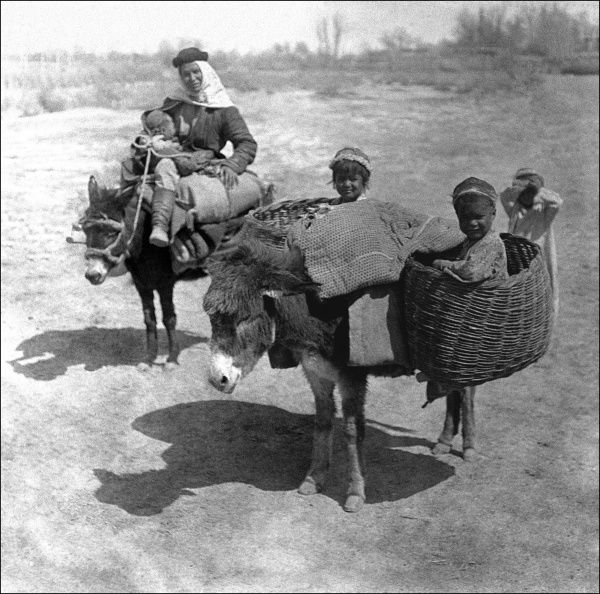A family of five -- mother and four children -- travelling through Kashgar, western China, on two donkeys