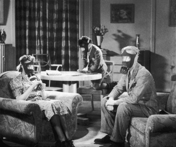 A family wearing gas masks on a quiet night in at home during World War II