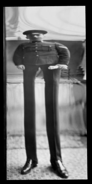 Fancy portrait of a soldier in a distorting mirror, with the lower part of his body elongated and the upper half shortened