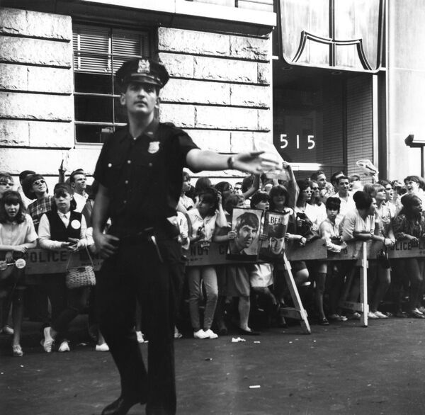 A New York police officer tries to keep control of young Beatles fans, two of them holding up photographs of George Harrison and Paul McCartney, as they wait... Date: September 1965