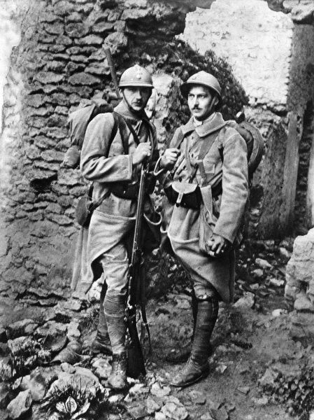 A French fusilier and trench-clearer standing together. The fusilier carries a Lebel rifle while the grenadier, or trench-clearer is equipped with a Browning pistol, knife and hand-grenades in order to clear captured enemy trenches