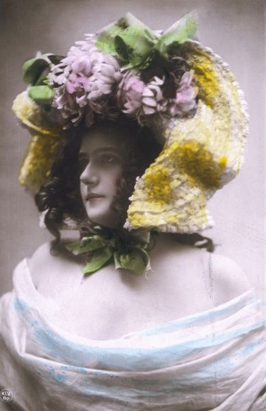 A young lady managing to keep a straight face while wearing a ludicrously large plaited straw hat profusely trimmed with flowers & bows & tied on like a bonnet with a ribbon