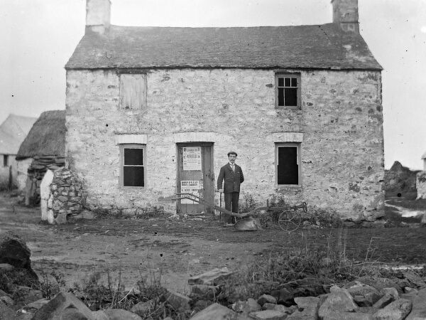 A rather run-down farm for sale at Solva, Pembrokeshire, Dyfed, South Wales. The windows are in a poor state, and one of them is boarded up. A man (perhaps the estate agent) stands proudly in front of the building with a plough at his feet
