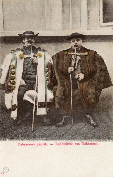 Farmers from Debrecen, Hungary, wearing incredible capes, smoking long-stemmed pipes and sporting fabulous waxed moustaches! Date: circa 1910s