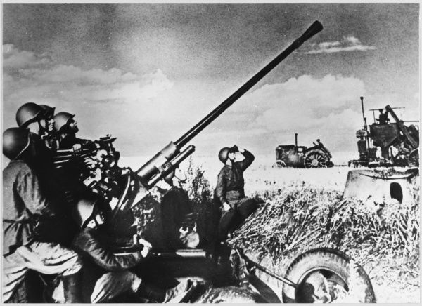 Soviet anti-aircraft guns provide protection for farmers near the battle front