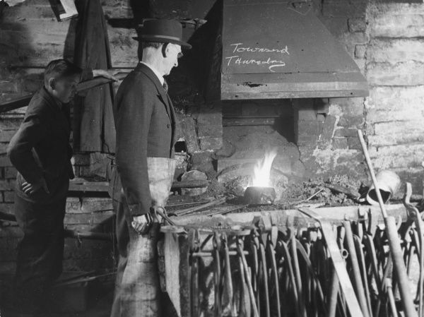 A farrier and his boy apprentice in a forge in Reading, Berkshire, England