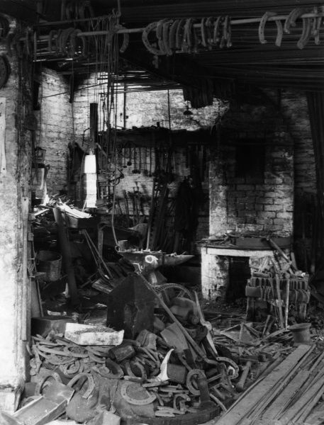 An interesting old farrier's shop at Ripley, Yorkshire, England, with horseshoes hanging from the ceiling. Date: 1930s