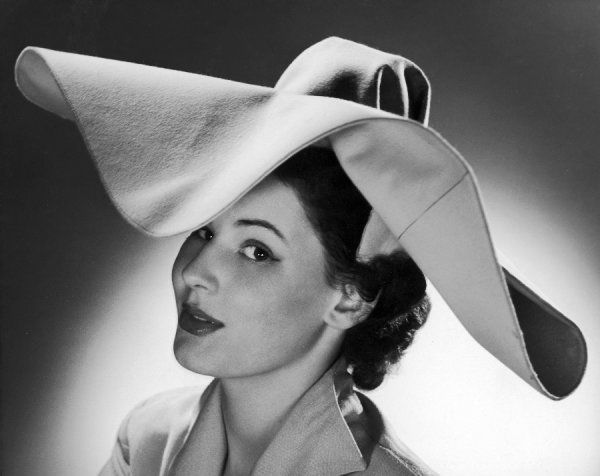 A woman wears a felt hat with a large, floppy brim