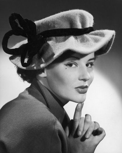 A woman wears a felt hat which has a felt ribbon tied around it. The model features a beauty spot on her cheek. Date: 1950s