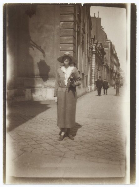A fashionable middle aged woman walks along a European street. She is wearing a long dress, a hat with a wide brim to shield her eyes from the sun, and carries a bag under her left arm