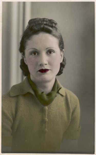 A fashionable young lady of the 1930s, with dark red lipstick and a light green woolly jumper and darker green scarf