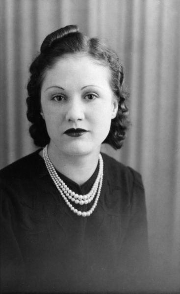 A fashionable young lady of the late 1930s, wearing a pearl necklace. Date: late 1930s