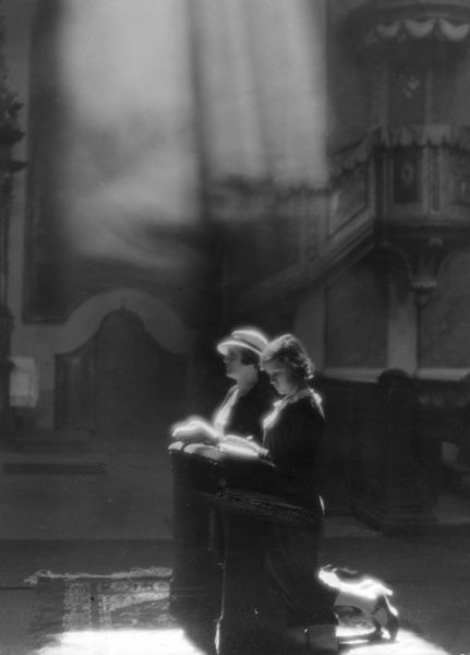 Fashionably devout : the sun shines on two kneeling women inside a church. Date: 1930s