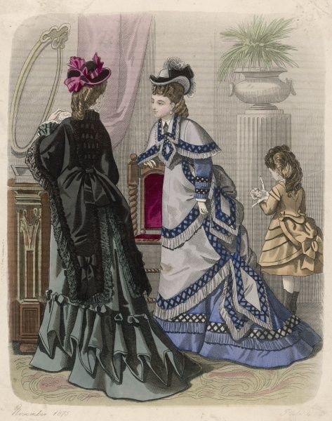Lace-edged mantle with tails; blue & grey dress with lattice trim, cape & over-skirts tied at the side over a trained skirt; girl in tunic with epaulettes & horizontal pleats