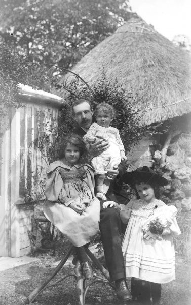A Father sits in a garden with his three daughters, one holding a toy doll and wearing a wide-brimmed hat