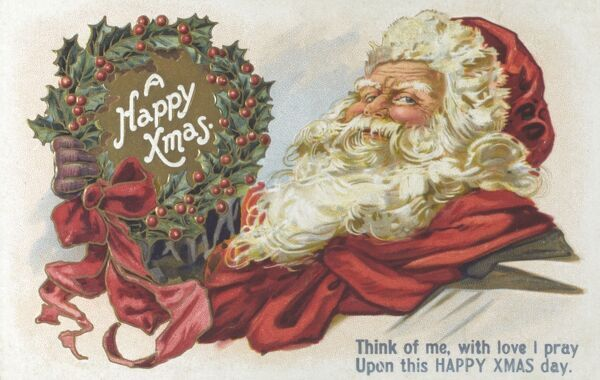 A Jolly Father Christmas holding up a Happy Xmas wreath. Date: circa 1910s
