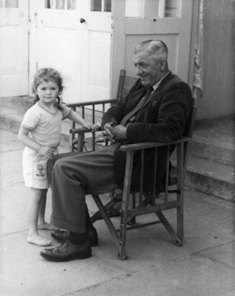 A father and his daughter outside their beach hut at a seaside resort. He looks at her, she looks at the camera. Date: late 1950s