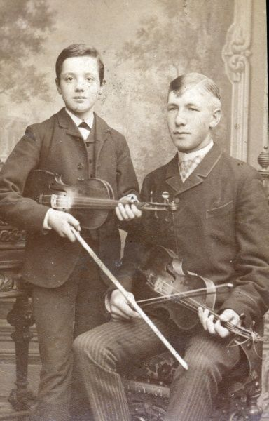 A father and his son posing with their violins. Date: c. 1910