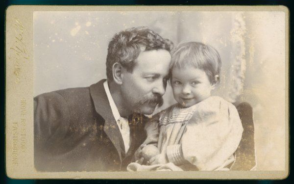 Informally posed portrait of a father and son; their heads resting against one another. The son, holding a ball, looks playfully at the camera; the father looks on tenderly