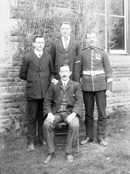 A family group photo in a garden, with a father and his three sons, one of them in uniform, during the First World War