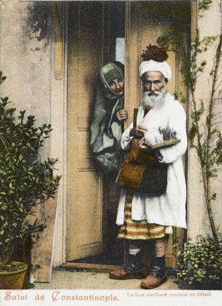 A door-to-door itinerant feather seller in Constantinople, Turkey. He also carries a bunch of grapes on his head!