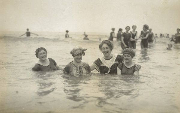 Four female bathers pose for a photograph in the sea
