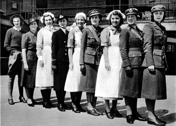 Photograph showing nine female employees of Harrods in their war-time uniforms, each woman working for a different 'service&#39