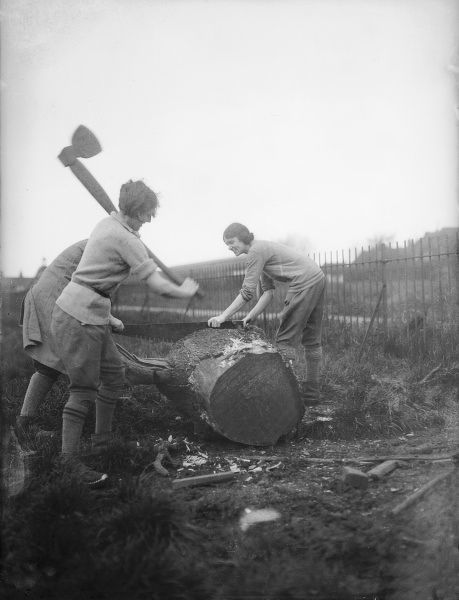 Two young women, female lumberjacks, chopping wood with huge axes on a college farm in Finchley, north London, England