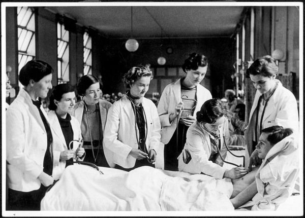 Under the watchful eye of the House Physician, a group of female medical students, trainee doctors, examine a patient at the Royal Free Hospital, Hampstead, London