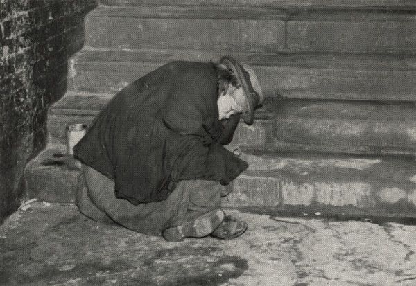 A female tramp sleeps on steps somewhere in Central London, where many of the city's homeless made their beds under bridges and railway arches. Date: circa 1930