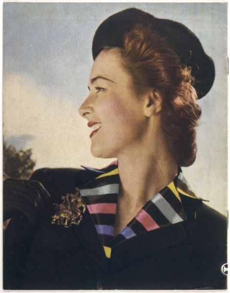 Smiling auburn haired woman sports a black beret worn at a rather rakish angle