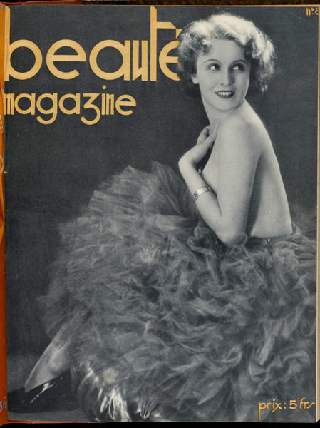 A lady sits and poses, in what looks like a tutu, and is perhaps topless with it