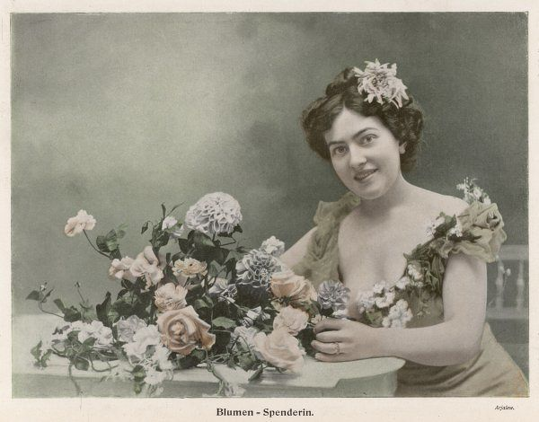 A smiling young woman with a flower in her hair & a garland of flowers adorning her dress, sits by a flower arrangement containing roses