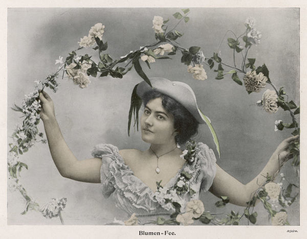 A young woman wearing a decollete dress, a glass locket & a felt hat with an upturned brim, holds aloft an arch composed of flowers