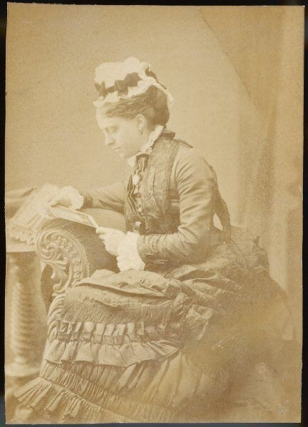 A young Victorian woman looking at a postcard. Date: late 19th century