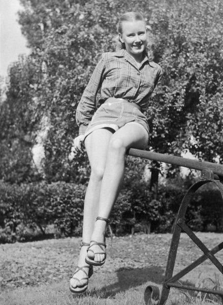 Young woman in casual clothes poses in the garden on a hot summer day