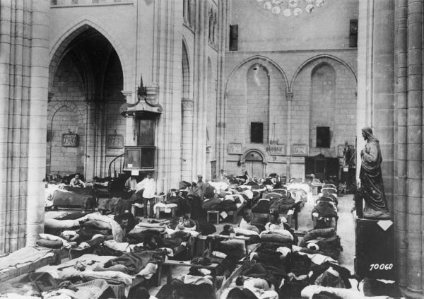 Wounded Allied soldiers lying in bed in a field hospital inside a church in Braisne, northern France, during the First World War. Date: 1914-1918