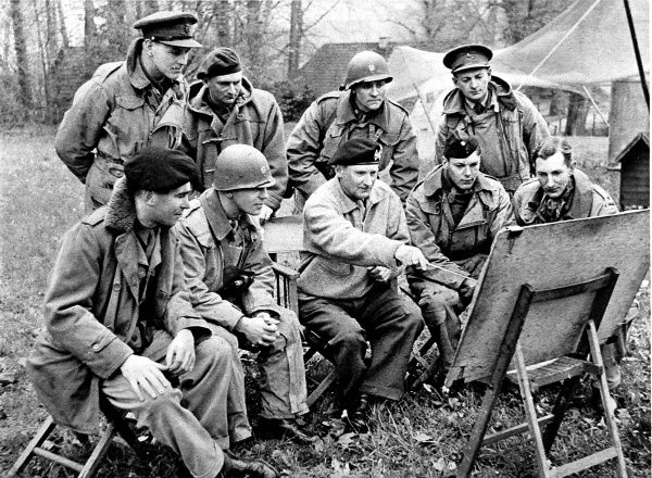 Photograph showing Field-Marshal Sir Bernard Montgomery (centre, pointing at map) briefing his liaison officers at his headquarters in Germany, April 1945