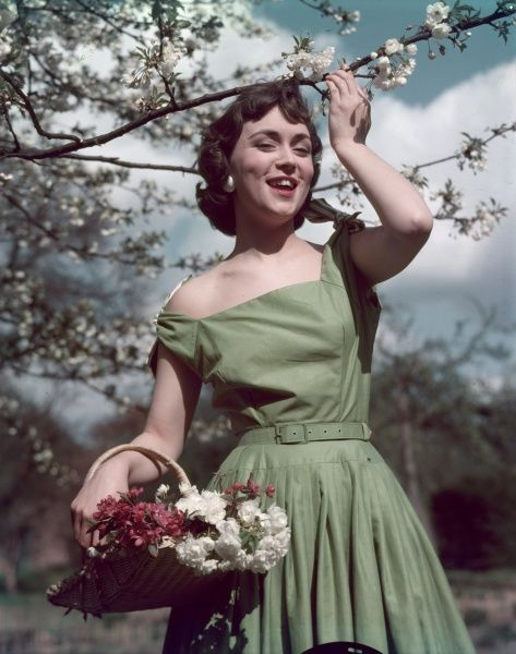 Outdoors girl wears a tailored summer frock with tie shoulder straps, square neckline, self- coloured belt & a full skirt with narrow pleats attached to a yoke