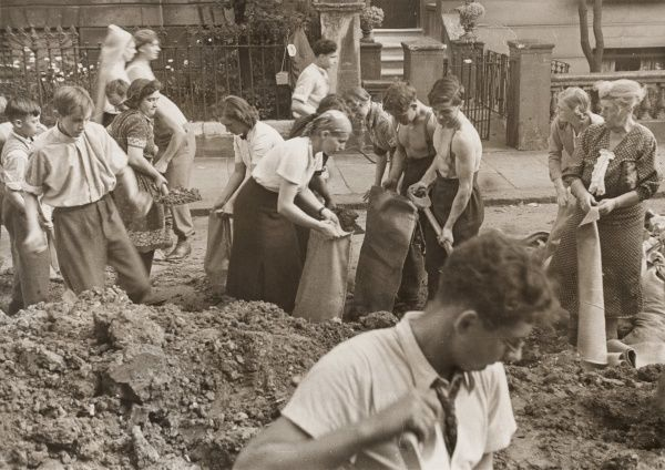 World War Two - British Home Front - London. Young men, boys and women of all ages fill sandbags in the street. The sandbags were piled against buildings and lower level windows to act as shock absorbers to negate the worst effects of bomb blasts