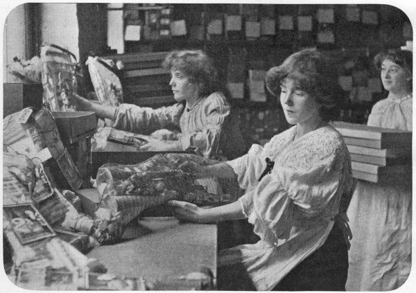 Female workers sit at tables filling net stockings with trinkets and toys at the Tom Smith Christmas cracker factory. Machines would cut out and sew the stockings and with this help, a girl would expect to complete 50 stockings an hour