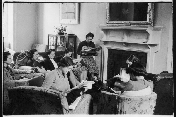 A group of proper young ladies, possibly at a finishing school or university, compose themselves and read newspapers around a gas fire. One girl is smoking