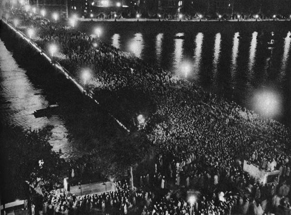 Westminster Bridge entirely covered in crowds of people enjoying a firework display on Coronation night. 1953
