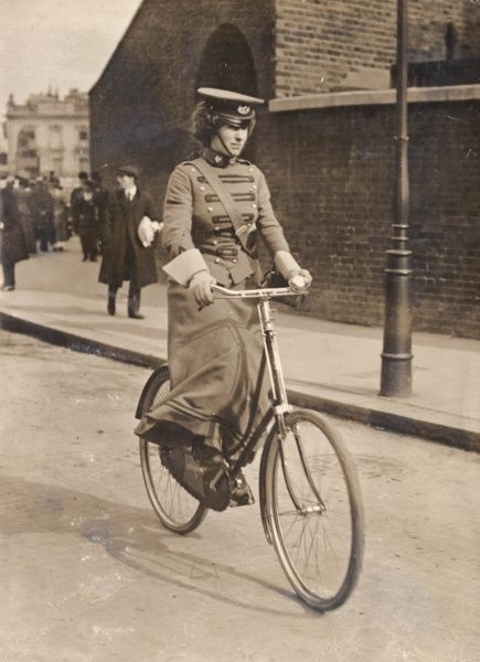 A woman cyclist first aid scout of the First Aid Nursing Yeomanry (FANY), riding along in her distinctive uniform