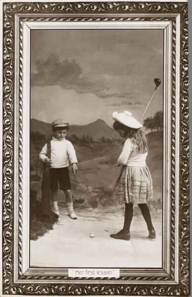 Her First Lesson. A young girl takes her first swing of a golf club, as her young boyfriend watches on an offer some advice along the lines of keeping her head still and her eye on the ball