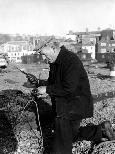 A fisherman mending nets at Hastings, Sussex -- there is black pitch on the net and on his hands