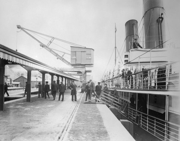 Scene at Fishguard Harbour and Railway Station, Pembrokeshire, South Wales, not long after the station opened. The dock leads straight into the station. A steamship from Ireland with two funnels has just arrived, and passengers are disembarking