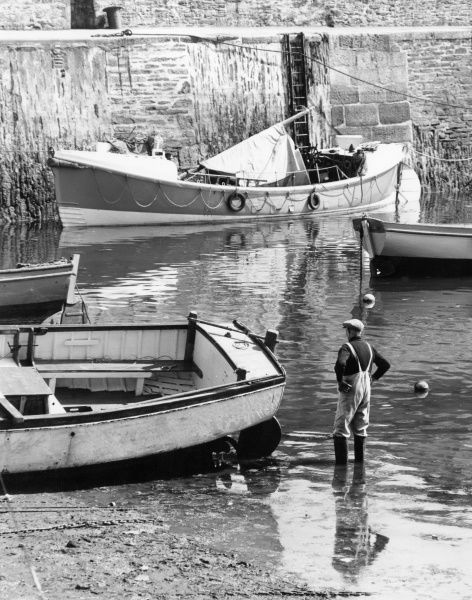 An old fisherman wades among fishing boats in a harbour, probably in Cornwall, England. Date: 1960s